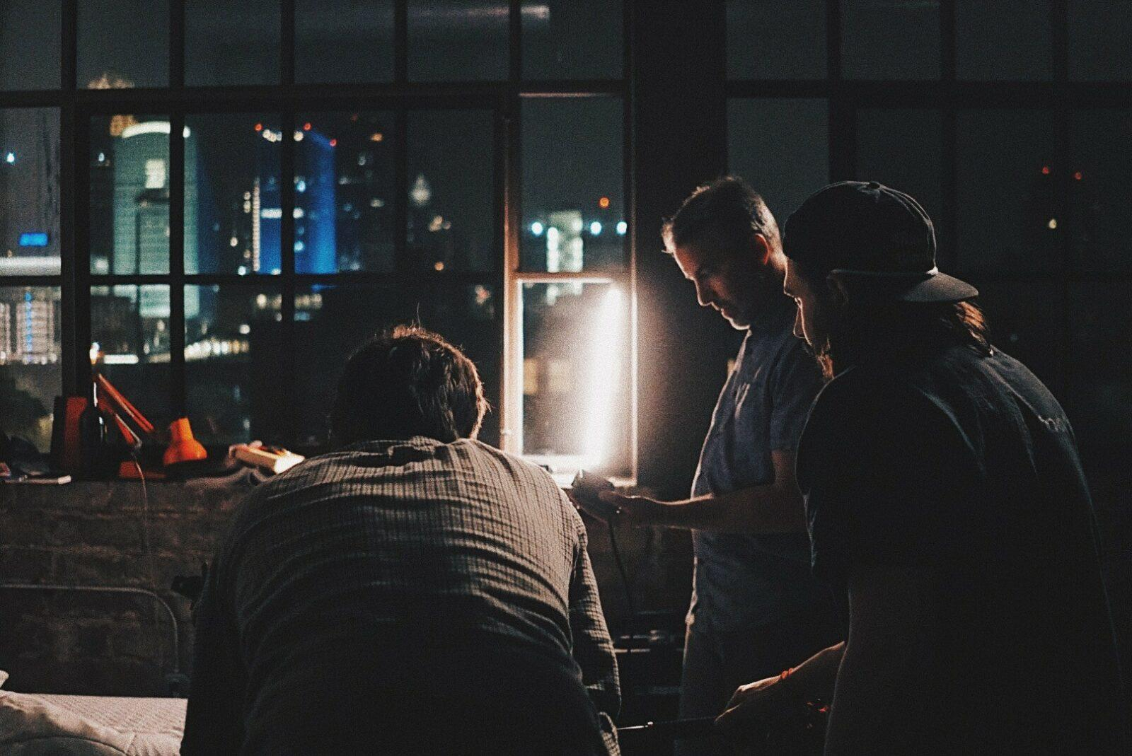 3 people standing around a desk at night,