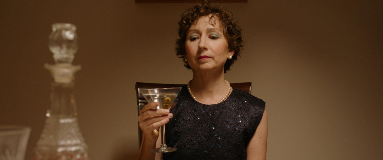 A woman drinkng a drink at a table.