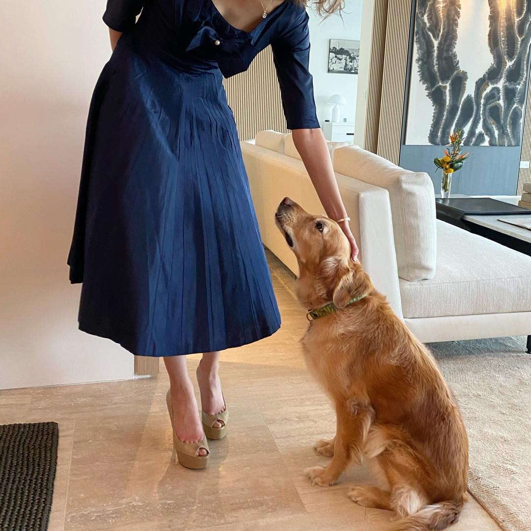 A woman in a dress petting a dog.