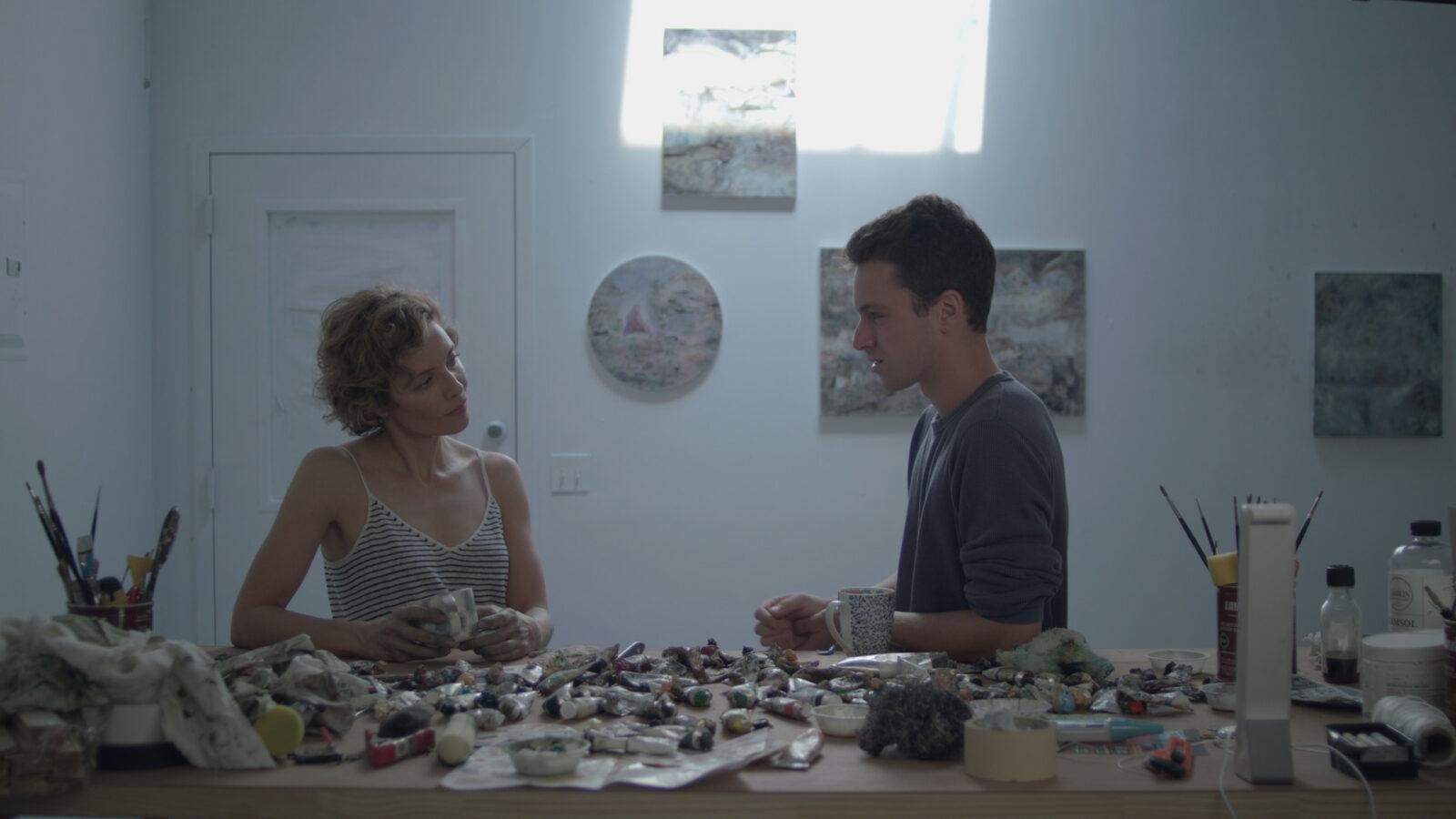 A man and a woman looking at each other with a bunch of paint on the table.