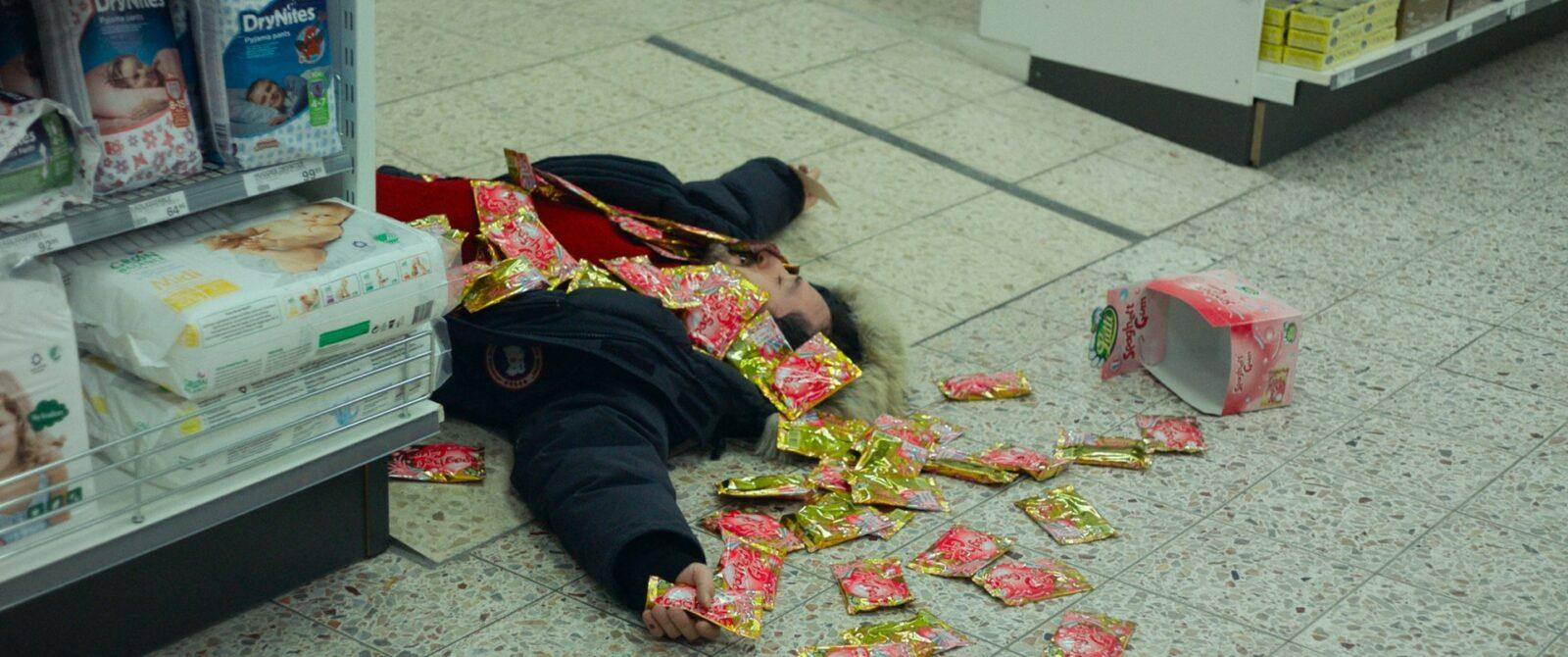 A man that fell over with a bunch of candies on the floor.