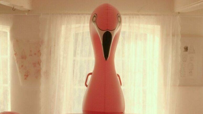 A flamingo floatie inside a house.