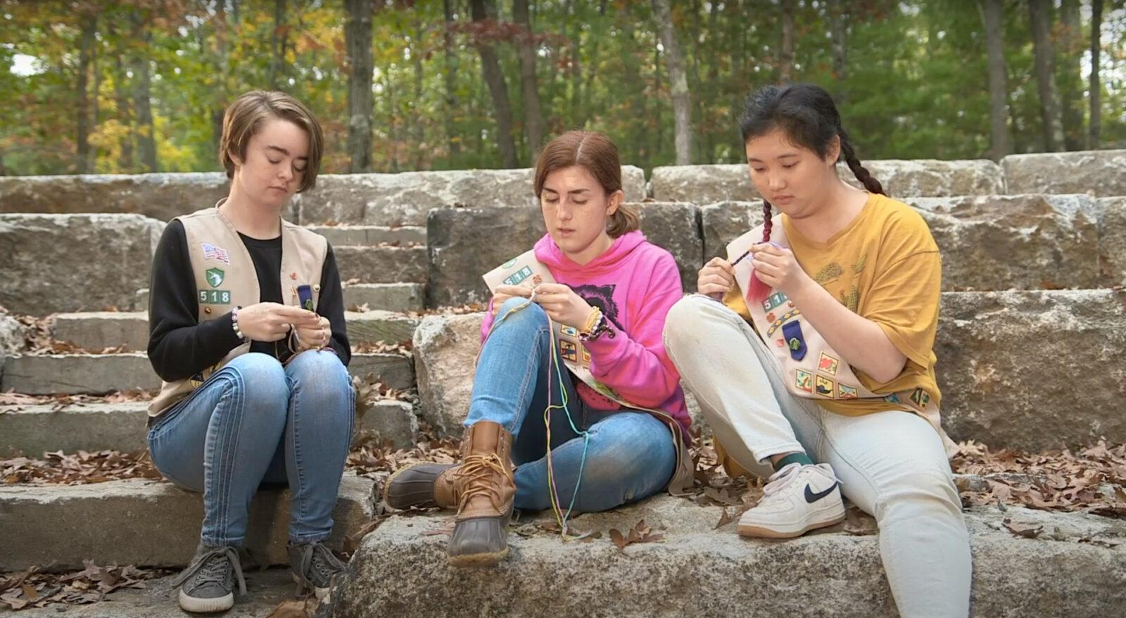 3 girls sitting down next to each other.