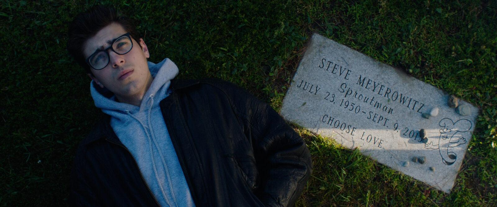 A man laying down next to a grave.