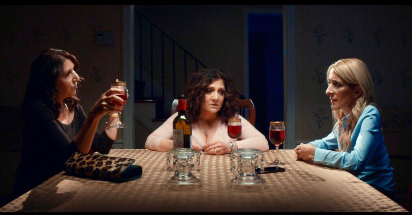 3 woman sitting around a table drinking wine.